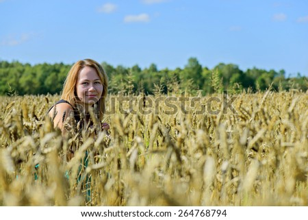 Portrait of young attractive of woman in field under the blue sky - stock photo