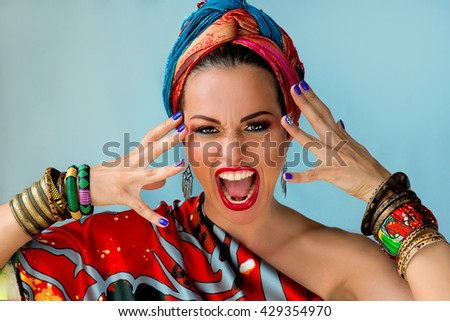 portrait of young attractive screaming woman in african style on colorful background - stock photo