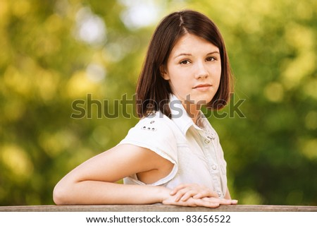 Portrait of young attractive seruous beautiful attractive brunette woman wearing white chemise at summer green park. - stock photo