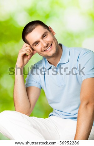 Portrait of young attractive smiling man, outdoors - stock photo