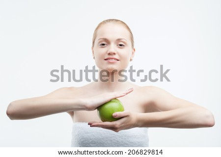 Portrait of young attractive smiling woman holding green apple in both hands, waistup portrait, isolated on white - stock photo