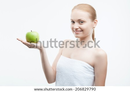 Portrait of young attractive smiling woman holding green apple on her palm, Waist up portrait, isolated on white - stock photo