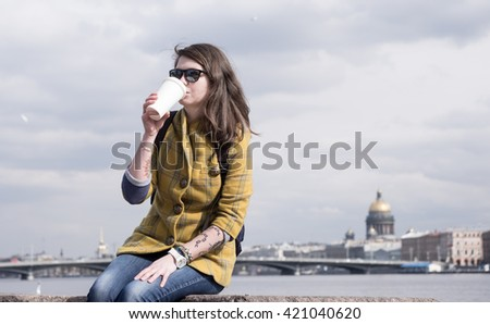 Portrait of young attractive tattooed  woman sitting on promenade and sight seeings as background - stock photo