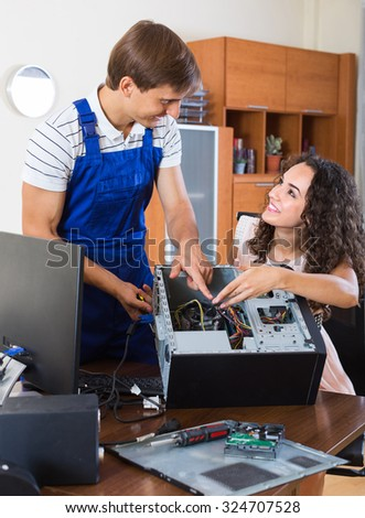 Portrait of young attractive woman and smiling PC specialist fixing broken computer indoors