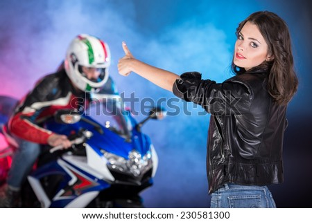 Portrait of young attractive woman. Biker on a motorcycle behind her on colored, foggy background. - stock photo
