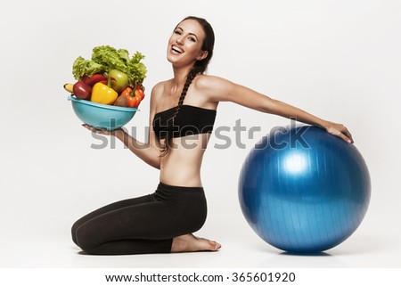 Portrait of young attractive woman doing exercises and holding bowl with fresh fruits and vegetables. Brunette with fit body holding fitness ball. Healthy lifestyle concept. - stock photo