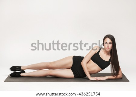 Portrait of young attractive woman doing exercises. Brunette with fit body on yoga mat. Healthy lifestyle and sports concept. Series of exercise poses. - stock photo