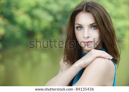 Portrait of young attractive woman embracing herself at summer green park.
