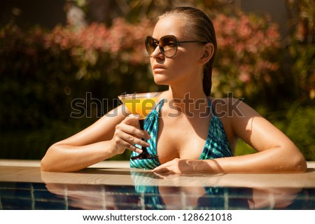 Portrait of young attractive woman having good time in swimming pool - stock photo