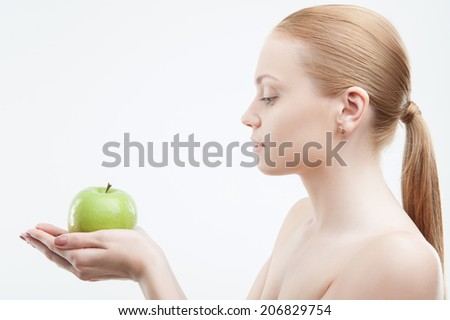 Portrait of young attractive woman holding green apple in both hands, side view portrait, isolated on white - stock photo