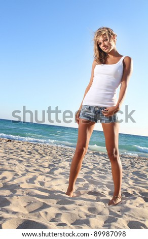 portrait of young attractive woman in black bikini on sky background