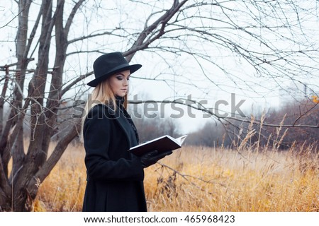 Portrait of young attractive woman in black coat and hat. She's one in a field reading book, autumn landscape, dry grass