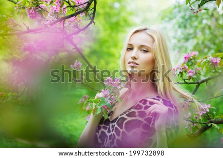 Portrait of young attractive woman in blooming spring trees. Outdoors portrait.