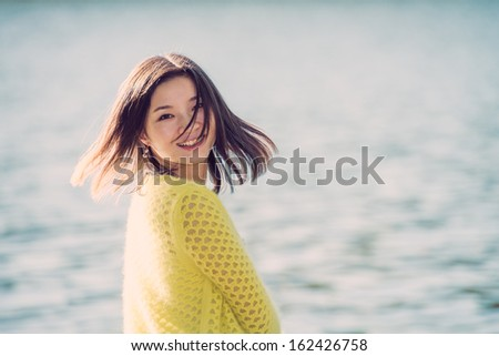 Portrait of young attractive woman sitting on a rock next to a river looking back with floating hair - stock photo