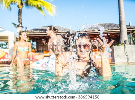 Portrait of young attractive woman splashing water in a swimming pool - Group of friends having party in a pool - stock photo