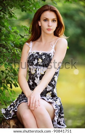 Portrait of young attractive woman wearing black dress sitting on stump against lake at summer green park.