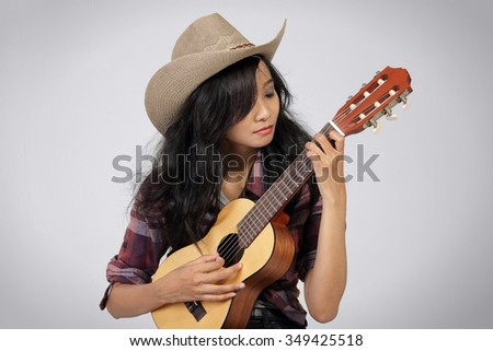 Portrait of young attractive woman wearing cowboy hat playing ukulele with closed eyes - stock photo