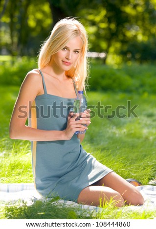 Portrait of young attractive woman with bottle of water, outdoors - stock photo