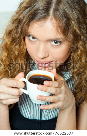 Portrait of young attractive woman with coffee on sofa. interior shot