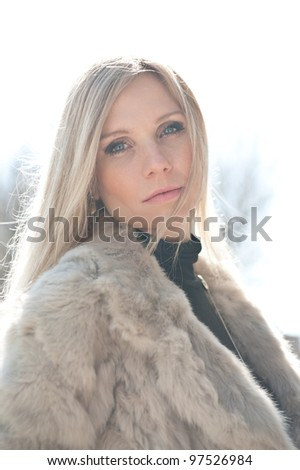 Portrait of young attractive woman with fur backlight.
