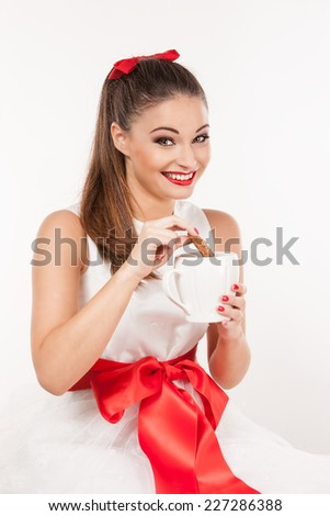 Portrait of young attractive woman with pinned-up ponytail with a red bow holding a mug and dipping  a cookie. Wearing a white christmas dress. - stock photo