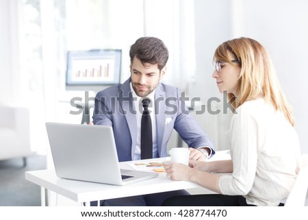Portrait of young bank officer consulting with businesswoman while sitting at office in front of laptop. - stock photo
