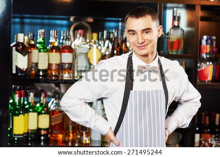 Portrait of young barman worker at bartender desk in restaurant bar  - stock photo