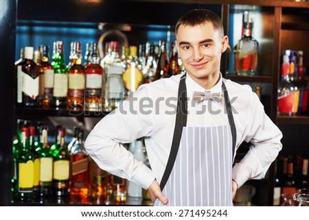 Portrait of young barman worker at bartender desk in restaurant bar  - stock photo