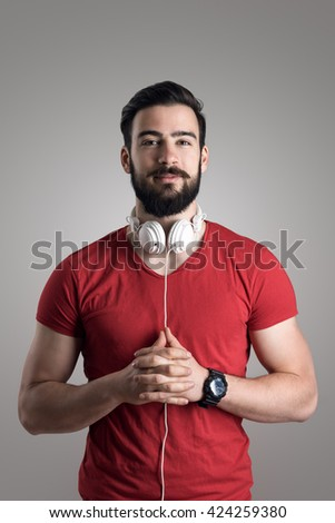 Portrait of young bearded man in red shirt with headphones around his neck - stock photo