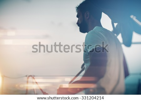 Portrait of young bearded man standing on a yacht and looking at the horizon. Visual effects - stock photo