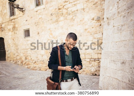 Portrait of young bearded man talking on his phone while walking in the street - stock photo