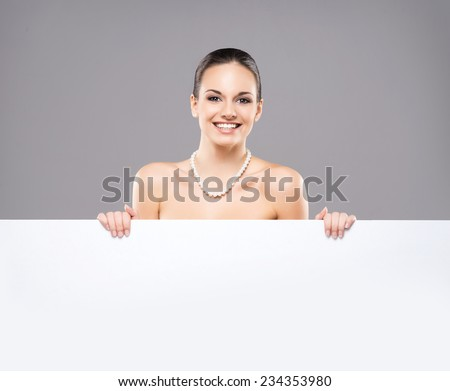 Portrait of young, beautiful and healthy woman in a pearl necklace and with a blank banner - stock photo
