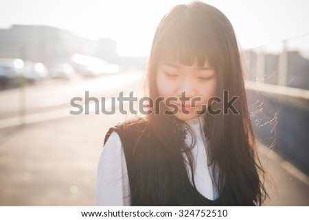 Portrait of young beautiful asian long brown straight hair hipster woman in the city, looking downward, pensive during sunset in backlight - thoughtful, thinking future, serious concept - stock photo