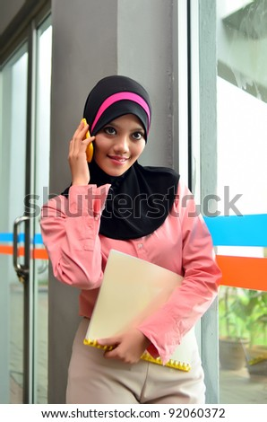 Portrait of young beautiful Asian Muslim women to talk business with a mobile phone while holding a file