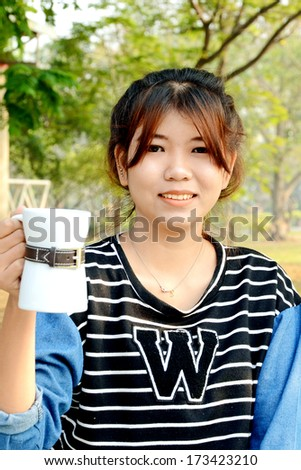 Portrait of young beautiful Asian woman drinking coffee in the garden under warm sunlight in the morning. - stock photo