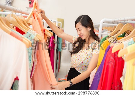 portrait of young beautiful asian woman shopping in clothing store - stock photo