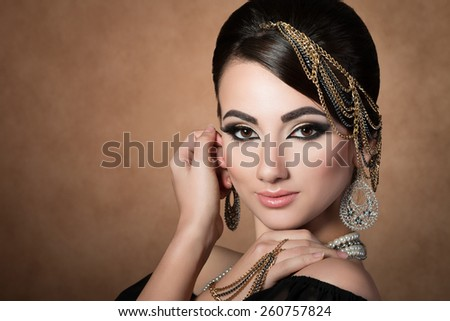 Portrait of young beautiful asian woman with evening make-up wearing head accessories and touching her face over beige background - stock photo