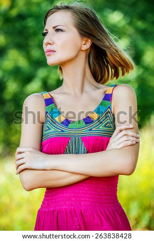 Portrait of young beautiful attractive dark-haired reflective woman at summer green park. - stock photo