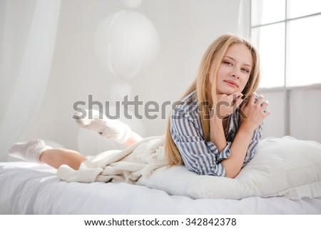 Portrait of young beautiful attractive female posing in her white bed in pajamas  - stock photo