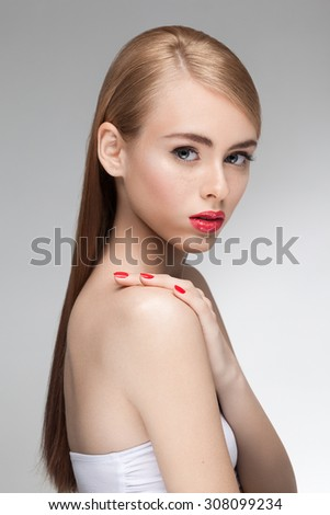 Portrait of young beautiful attractive girl model with natural fresh beauty, perfect clean skin and nude makeup: black eyeliner and red lipstick, red nail polish and blonde straight hair. Sensual pose - stock photo