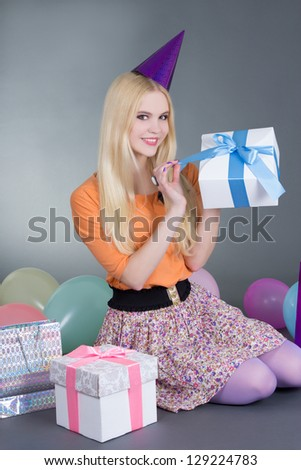 portrait of young beautiful blond with gift over grey