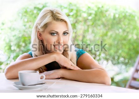 Portrait of young beautiful blond woman with cup of coffee sitting in cafe outdoor  - stock photo