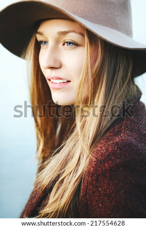 Portrait of young beautiful blonde girl with fresh clean skin and blue eyes. Wearing hat and jacket. Outside - stock photo