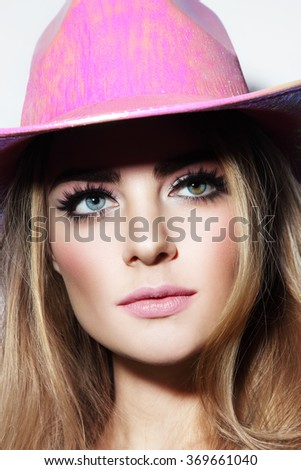 Portrait of young beautiful blonde girl with stylish make-up in party pink cowboy hat - stock photo