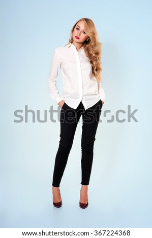 Portrait of young beautiful blonde in white blouse and black pants - stock photo