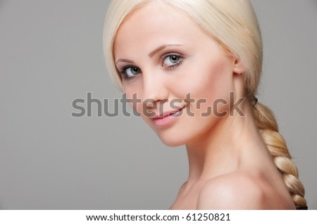 portrait of young beautiful blonde over grey background - stock photo