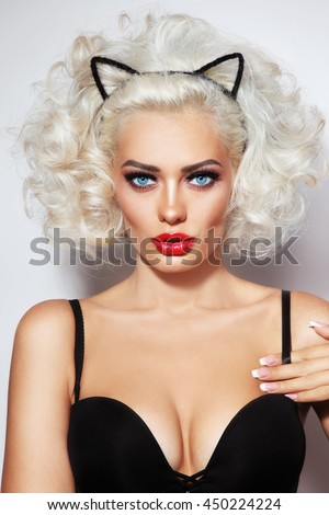 Portrait of young beautiful blonde sexy woman with fancy hairdo and cat ears headband - stock photo