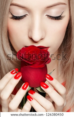 portrait of young beautiful blonde woman closing eyes and holding red rose in manicured hands - stock photo
