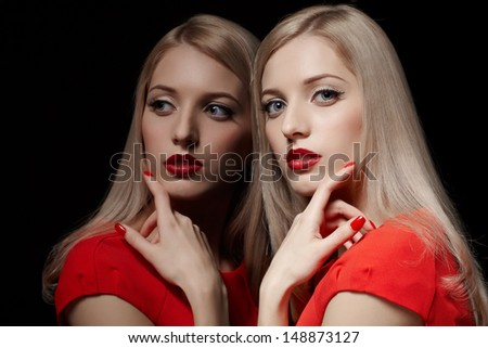 portrait of young beautiful blonde woman in red dress touching her cheek with manicured finger at mirror