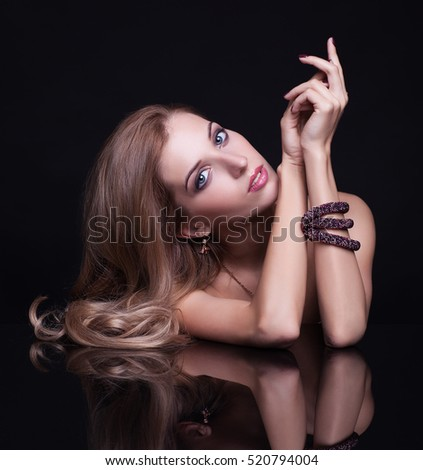 Portrait of young beautiful blonde woman sitting at mirror table on black background